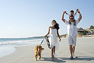 Family walking on the beach with dog - ABAF02132
