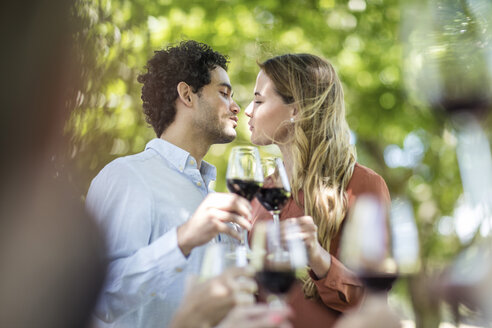 Couple kissing during lunch in garden with red wine - ZEF12364