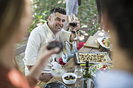 Friends and family having lunch in garden with red wine - ZEF12367