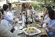 Adult daughter embracing father during lunch in garden - ZEF12370