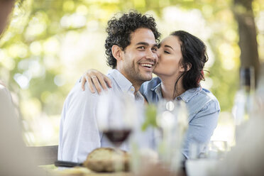 Young woman kissing a happy young man at outdoor table - ZEF12376