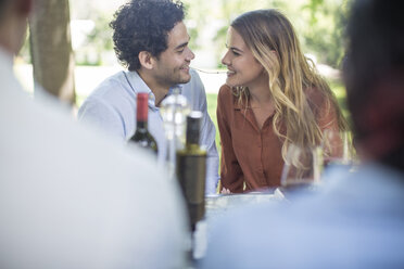 Couple sharing spaghetti at outdoor table - ZEF12379