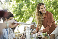 Smiling woman dishing up at family lunch in garden - ZEF12382