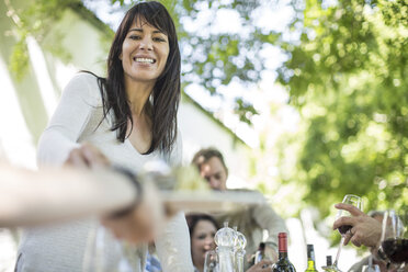 Smiling woman at family lunch in garden - ZEF12394