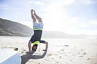 Man doing a headstand on the beach - ABZF01709