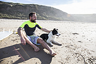 Man with dog and surfboard on the beach - ABZF01712