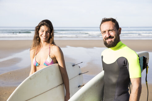 Happy couple carrying surfboards on the beach - ABZF01715