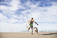 Man carrying surfboard running with dog on the beach - ABZF01730