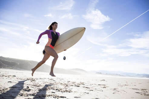 Woman carrying surfboard running on the beach - ABZF01733