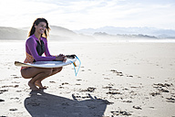 Smiling woman with surfboard crouching on the beach - ABZF01736