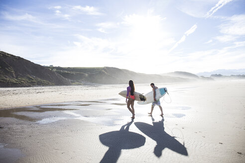 Couple carrying surfboards walking on the beach - ABZF01739