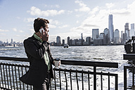 USA, businessman on cell phone at New Jersey waterfront with view to Manhattan - UUF09691