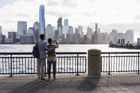 USA, man and woman at New Jersey waterfront with view to Manhattan - UUF09697