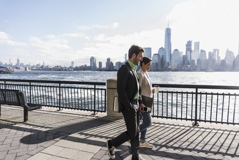 USA, man and woman walking at New Jersey waterfront with view to Manhattan - UUF09700