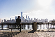 USA, man sitting on bench at New Jersey waterfront with view to Manhattan - UUF09712