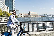 USA, man on bicycle at New Jersey waterfront with view to Manhattan - UUF09715
