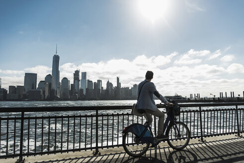 USA, man on bicycle at New Jersey waterfront with view to Manhattan - UUF09718