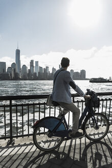 USA, man on bicycle at New Jersey waterfront with view to Manhattan - UUF09721