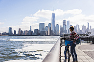 USA, woman with bicycle at New Jersey waterfront with view to Manhattan - UUF09730