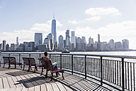 USA, woman sitting on bench at New Jersey waterfront with view to Manhattan - UUF09733
