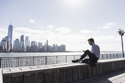 USA, man using tablet at New Jersey waterfront with view to Manhattan - UUF09736