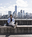 USA, man wearing headphones using tablet at New Jersey waterfront with view to Manhattan - UUF09751