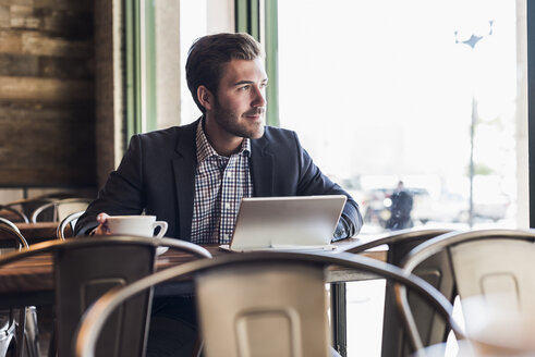 Businessman using tablet in a cafe - UUF09754