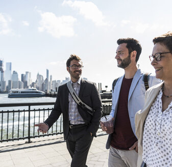 USA, colleagues walking at New Jersey waterfront with view to Manhattan - UUF09757