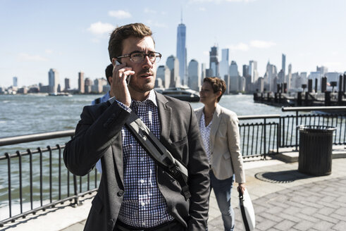 USA, businessman on cell phone at New Jersey waterfront with view to Manhattan - UUF09760