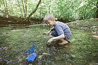 Boy playing with a toy boat in a forest brook - RBF05527