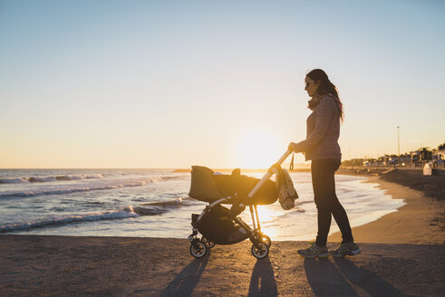 Woman walking with a stroller on the seashore at sunset - GEMF01367