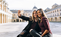 Two smiling young women on urban square taking a selfie - MGOF02754
