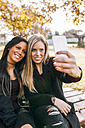Two smiling young women on park bench taking a selfie - MGOF02757