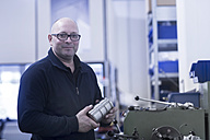 Portrait of man in a factory holding steel - SGF02080