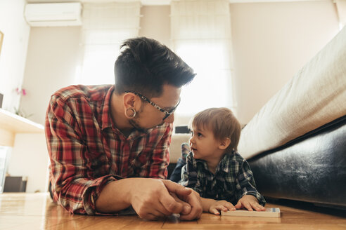 Father and son lying on the floor with a book - ZEDF00497