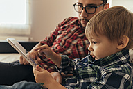 Father and son on couch using tablet - ZEDF00500