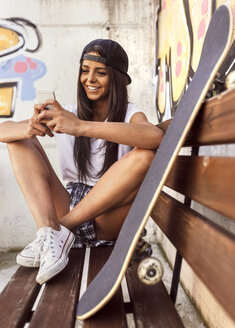 Smiling young woman with skateboard looking at cell phone - MGOF02767