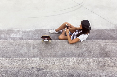 Young woman with skateboard looking at cell phone - MGOF02770