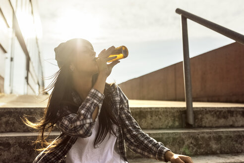 Young woman sitting on stairs drinking a beer from the bottle - MGOF02776