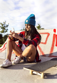 Young woman with skateboard and cell phone in a skatepark - MGOF02782