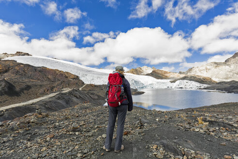 Peru, Andes, Cordillera Blanca, Huascaran National Park, tourist standing at shore of Pastoruri glacier lake - FOF08556