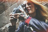 Tattooed woman's hands holding  reflex camera - KIJF01042
