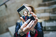 Tattooed woman's hands taking  selfie with smartphone, close-up - KIJF01045