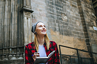 Spain, Barcelona, smiling young woman with notebook - KIJF01054