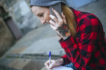 Tattooed young woman talking on mobile phone - KIJF01057