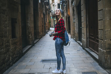 Spain, Barcelona, young woman taking pictures with reflex camera at Gothic Quarter - KIJF01060