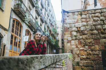 Spain, Barcelona, young woman taking pictures with camera at Gothic Quarter - KIJF01066