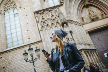 Spain, Barcelona, young woman with mobile phone watching something - KIJF01072