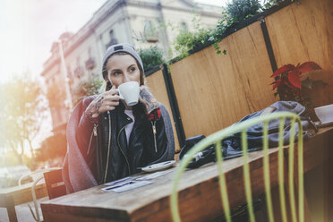 Young tattooed woman sitting in pavement cafe drinking coffee - KIJF01075