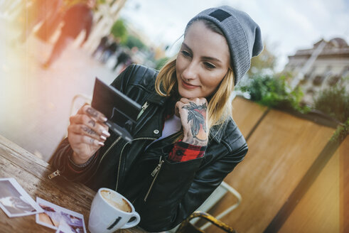 Young tattooed woman sitting in a pavement cafe looking at photos - KIJF01078